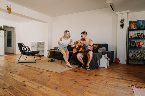 couple sitting on couch. man playing guitar.