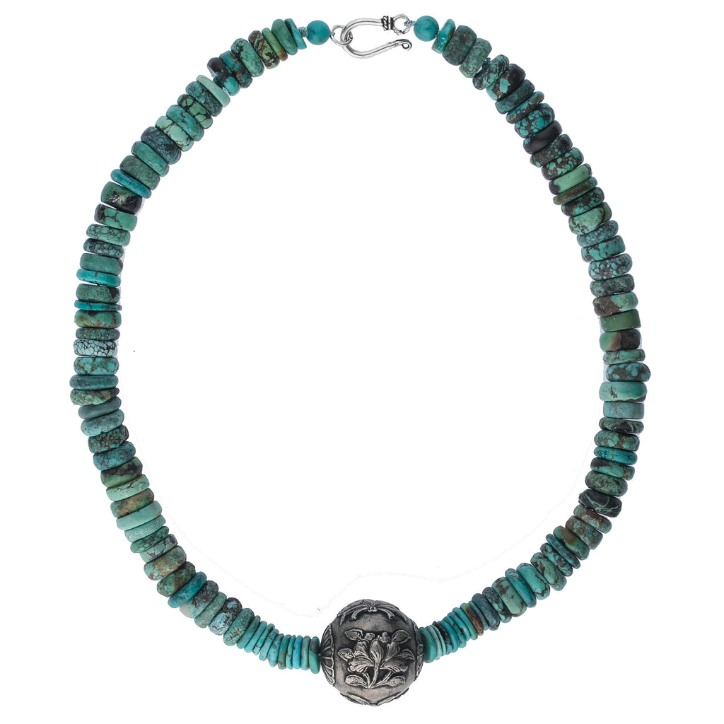 Turquoise heishi necklace with a hand-worked Chinese repoussé coin silver bead. Sterling hook clasp. nlbd1261