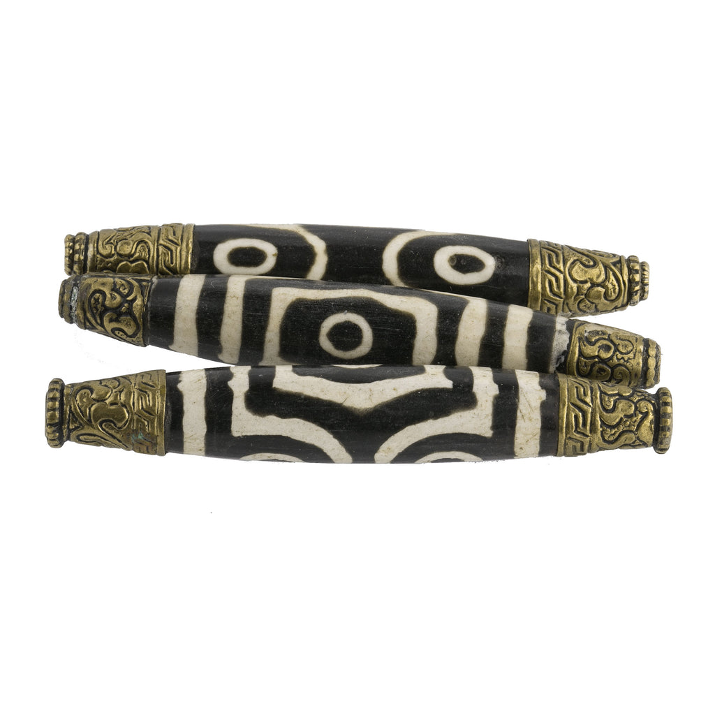 Vintage reproduction of an antique 3 to 6 eyeTibetan dZi bead capped in repoussé brass. 82x13mm. b10-0432