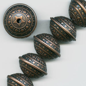 b18-0289- Copper plated rounded disk with fancy embossed design.
