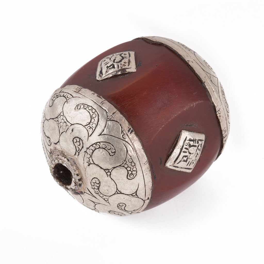 Tibetan large amber resin bead with repousse sterling silver caps applied etched silver medallions.Nepal 1970s. 40x34mm. b4-amb092