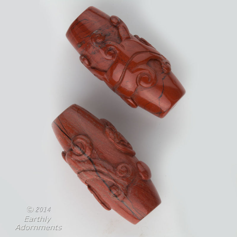 Carved red jasper tapered cylinder in a salamander design that wraps around the bead. 40x20mm. Sold individually. b4-jas244
