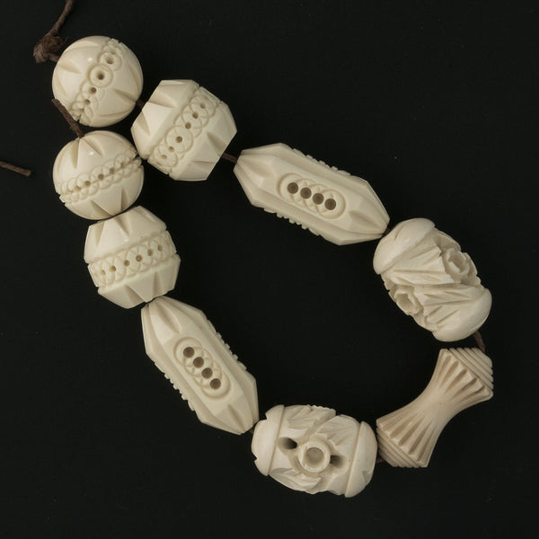 Strand of 9 vintage carved celluloid beads. c. 1930s. b6-228(e)
