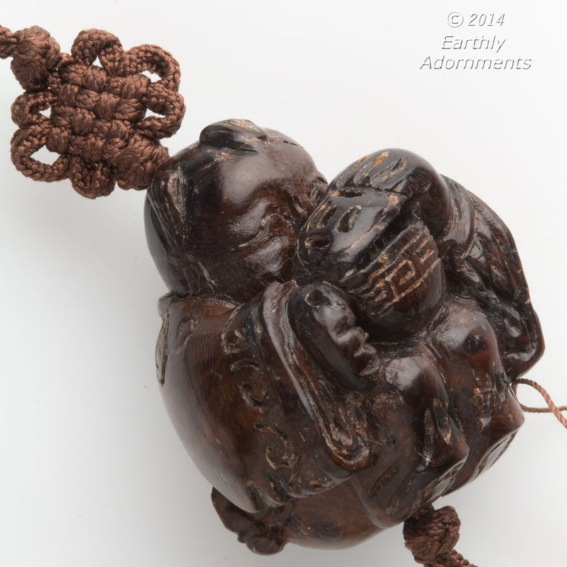 Vintage hardwood carved bead depicting a boy peering into a lidded rice bowl. with cord and tassel. China 1970's. b7-wo328(e)