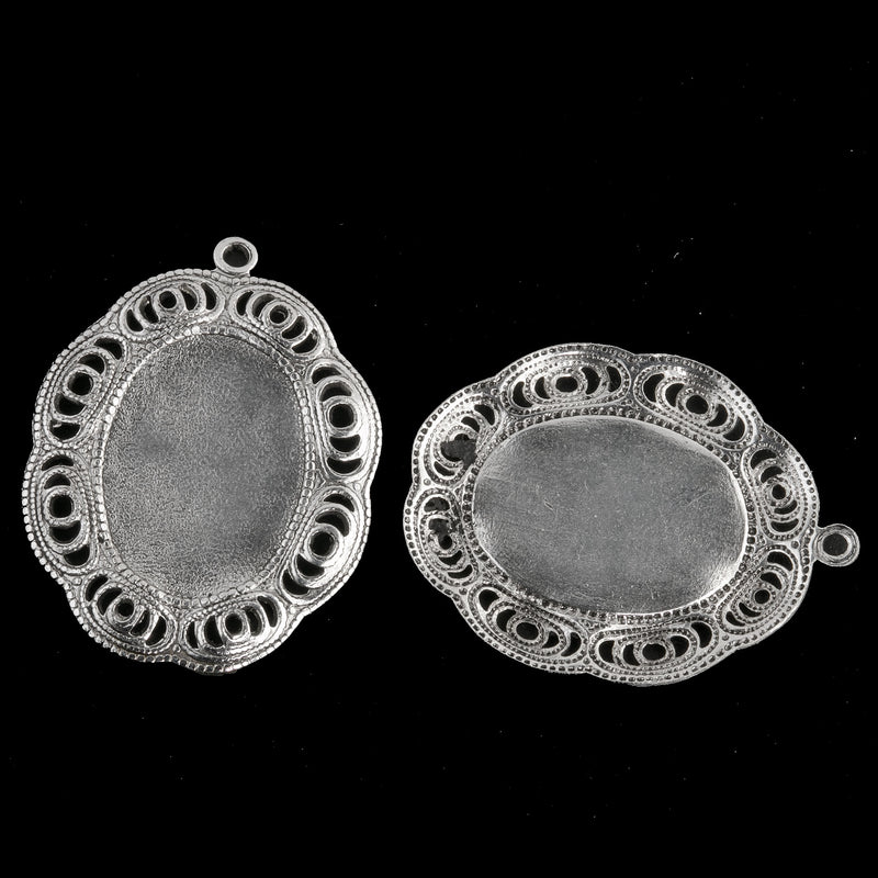 Sterling silver plated brass oval solid back setting for 19x13mm cabochon. Wavy filigree border. 1 ring. Sold individually. b9-2426