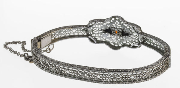 brad106(e)- 1930s Art Deco hinged rhodium filigree bangle bracelet with red and black glass stones.