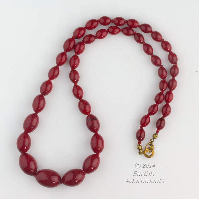 Vintage necklace of graduated Japanese crimson red glass oval beads with brass spring clasp. 19