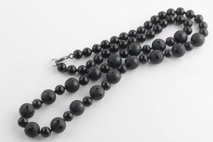 Vintage hand knotted necklace of black onyx beads, frosted with polished stars. nlbd1178