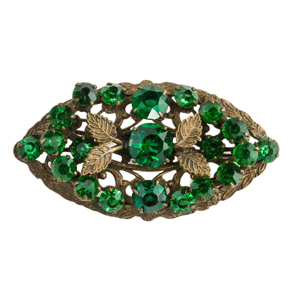Vintage stamped brass filigree oval brooch with a cluster of prong set faceted emerald green glass stones and brass leaves. 1930s. pnbg1013