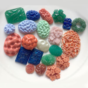 "A grab bag of pressed and ""carved"" glass cabochons. Largest stone is 17 x 27, b19-001"