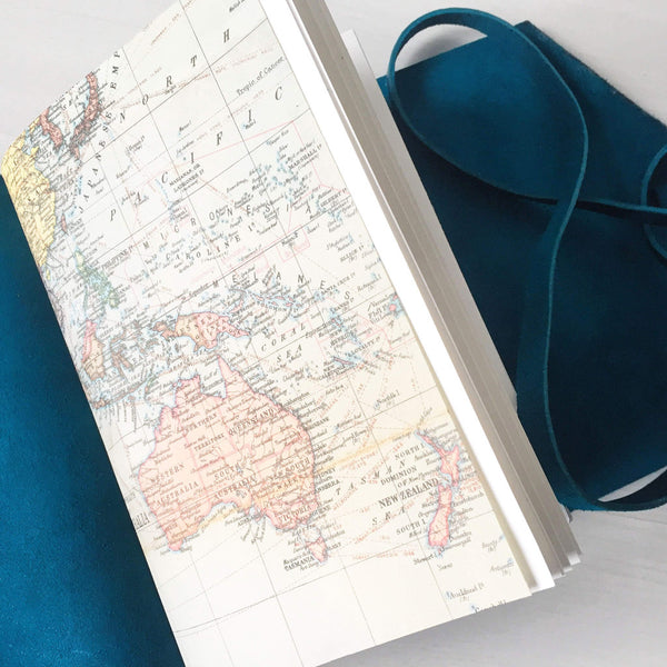 world map pages in open leather bound book