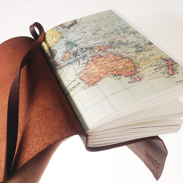 Hand holding open leather bound book with world map pages