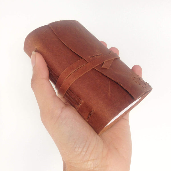Hand holding a tan leather pocket notebook