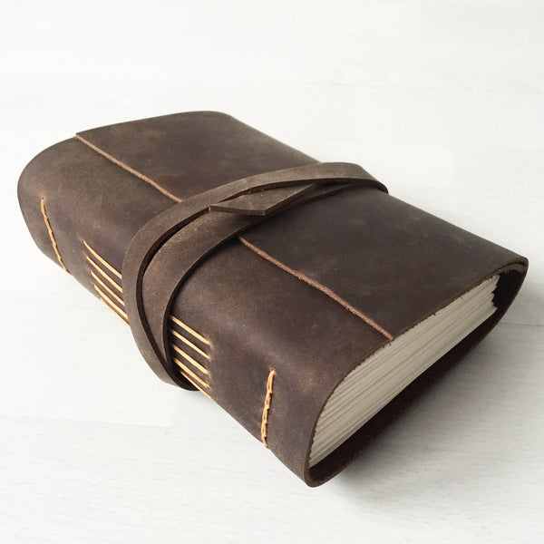 Brown leather bound journal, butterscotch longstitch binding, side angle view