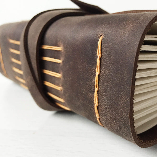 Close up side view of longstitch binding, brown with butterscotch stitching