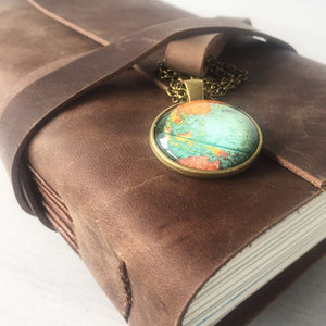 Long stitch bound brown leather journal with world map globe charm at strap