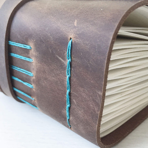 Brown leather bound journal with teal longstitch binding, side angle view