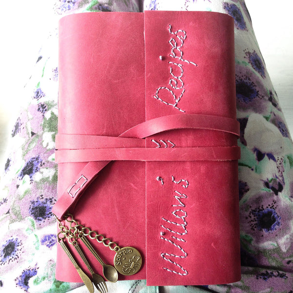 Pink leather custom recipe book with hand stitched name on cover and cutlery charms