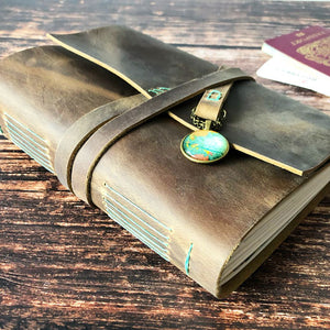 Brown leather bound travel journal with world map globe charm