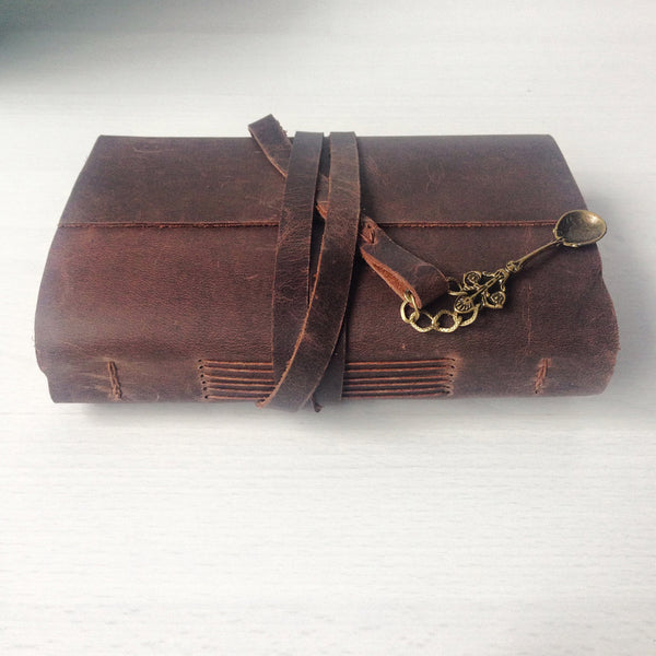 Brown leather recipe journal with spoon charm, side view