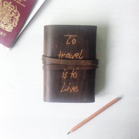 Brown leather journal front view of hand stitched To travel is to live quote
