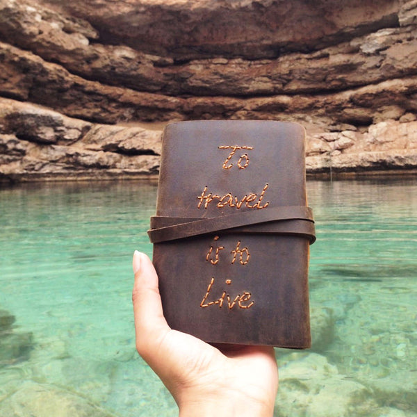 Hand in frame holding To travel is to live handstitched quote journal in a sinkhole, Oman