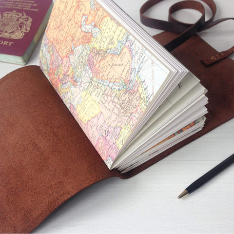 A6 Brown leather travelers notebook with world map pages side angle view