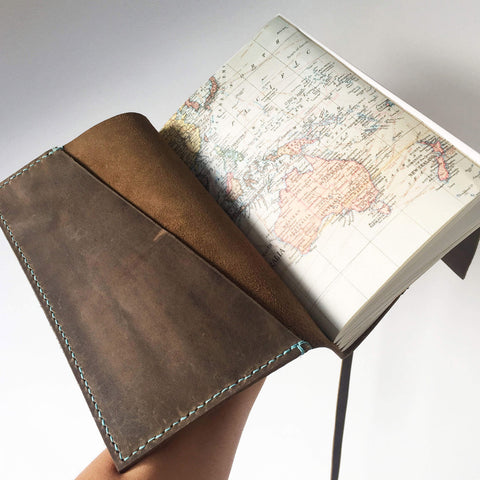 Opened view of A5 world map travel journal with saddle stitched pockets