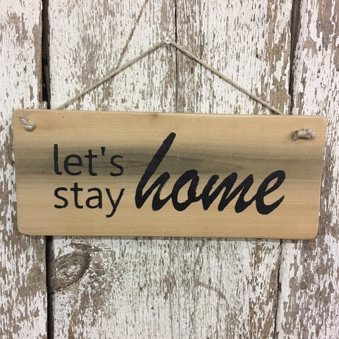 Lets stay home sign painted in black on reclaimed upcycled wood