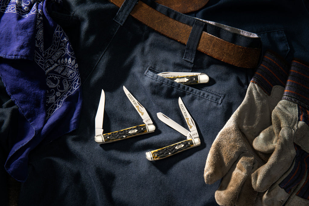 Knives displayed on background of pants and work gloves.