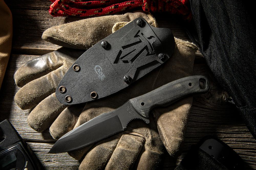 Case® X Winkler Smooth Black Canvas Laminate Kyle Lamb Hunter showing the front of the knife and sheath; laying on leather workmans gloves
