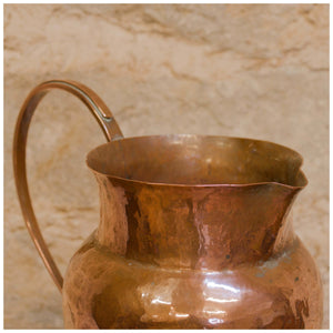 An Arts & Crafts Lakes School hand beaten copper jug by Fanny Carter