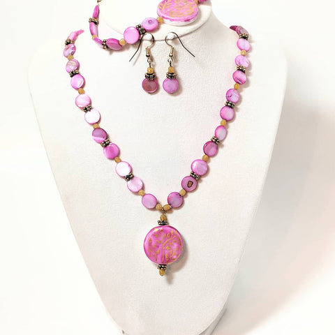 Three piece Pretty In Pink set: A necklace, bracelet, and pair of earrings. Each item is made of pink, shell disc beads and topaz yellow crystals.