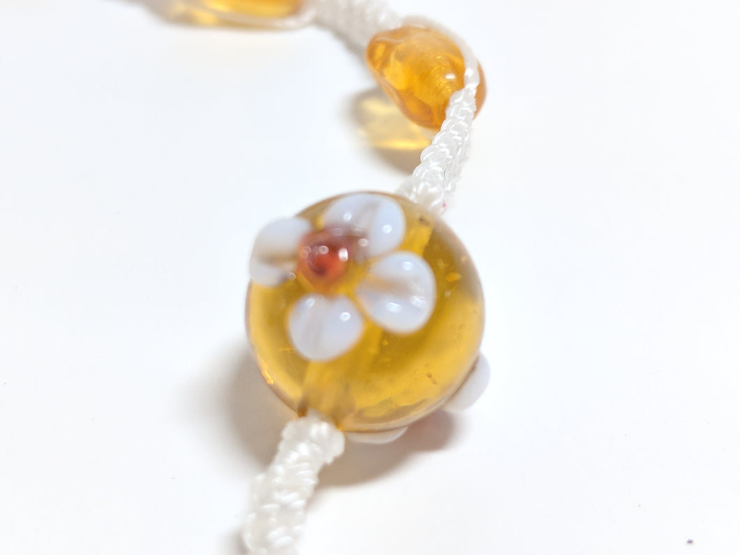 Close up view of Amber with white flower round glass bead