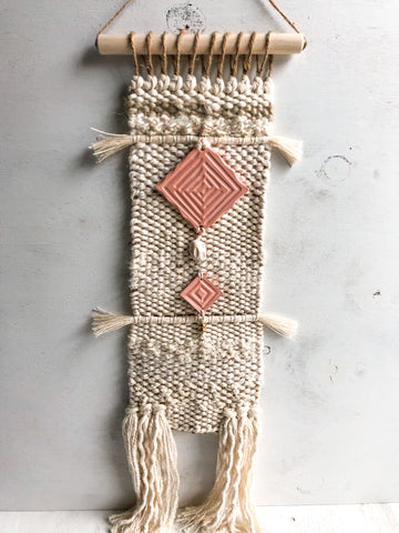 Handwoven wall hanging with ceramic detail