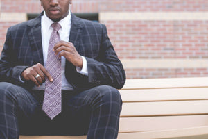 Man in custom suit sitting on bench.