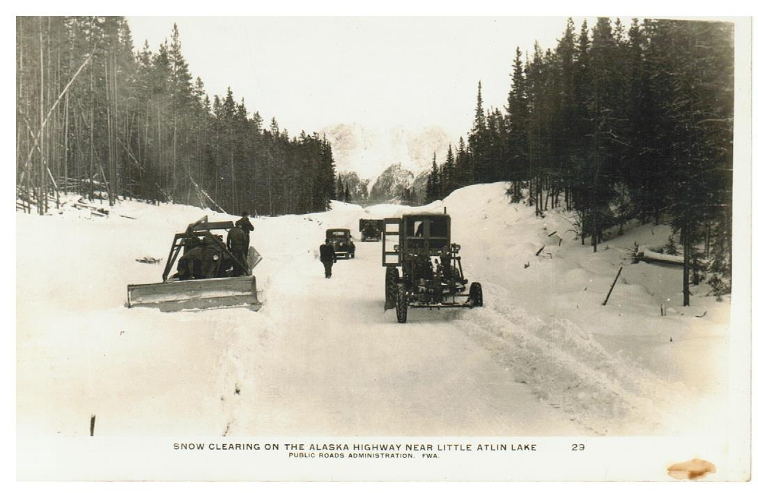 ALASKA HIGHWAY. RPPC POSTCARD. SNOW CLEARING BY GRADERS NEAR LITTLE ATLIN LAKE, BC. CANADA