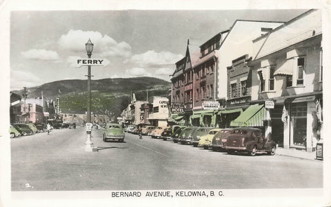 Kelowna, British Columbia 1950's Bernard Ave Street Scene With Storefronts. Canada RPPC Postcard