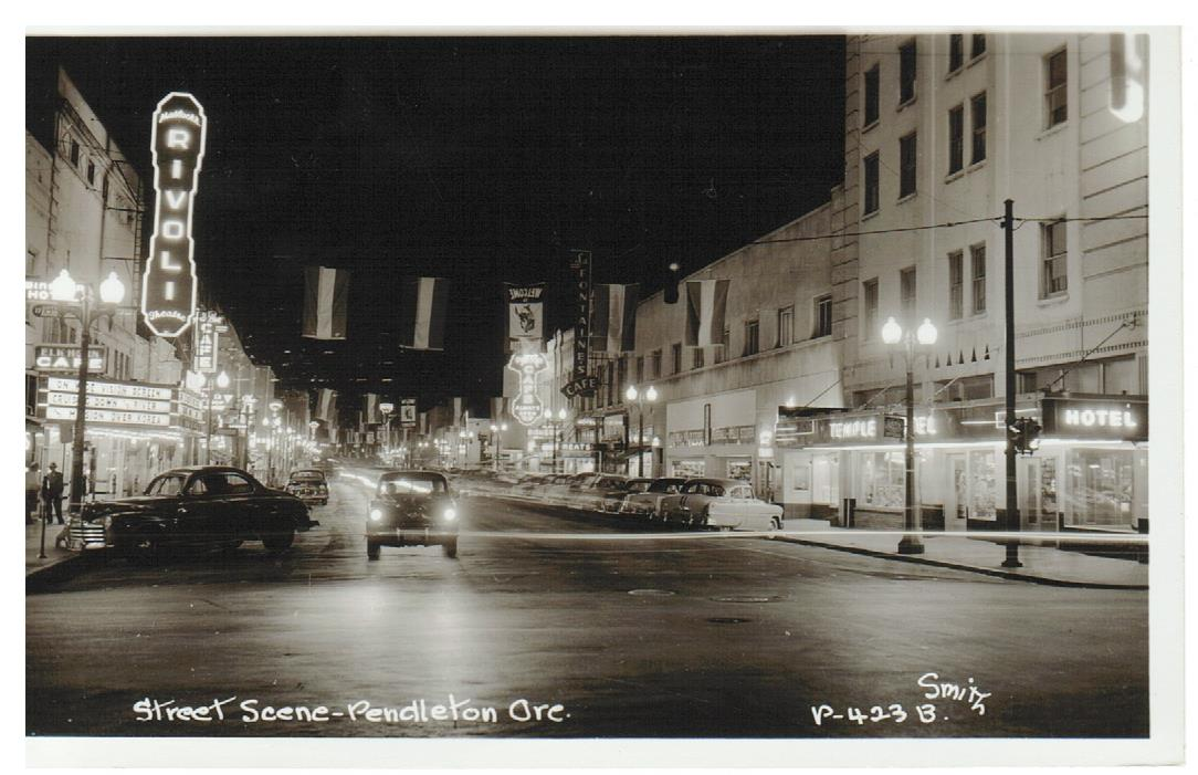 Pendleton, Oregon. RPPC Postcard.  Night Scene. Rivoli Theater. Temple Hotel and Cafe's.