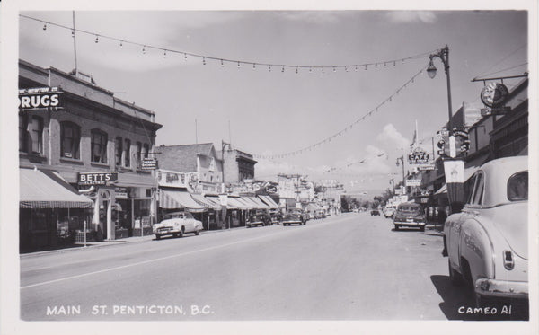 BC. Penticton. RPPC. Postcard. Main Street. BETT'S. More cars respecting Social Distancing. British Columbia, Canada