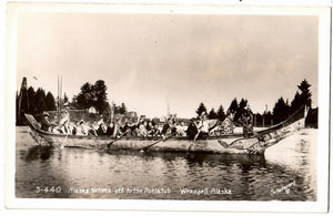 INDIGENOUS PEOPLE IN LARGE CANOE TO ATTEND POTLACH RPPC POSTCARD WRANGELL, ALASKA