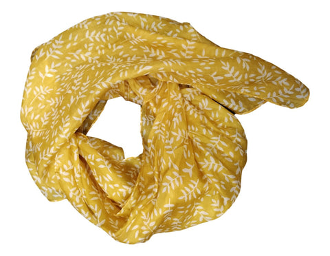 A mustard yellow silk scarf with a design of small cream leaves