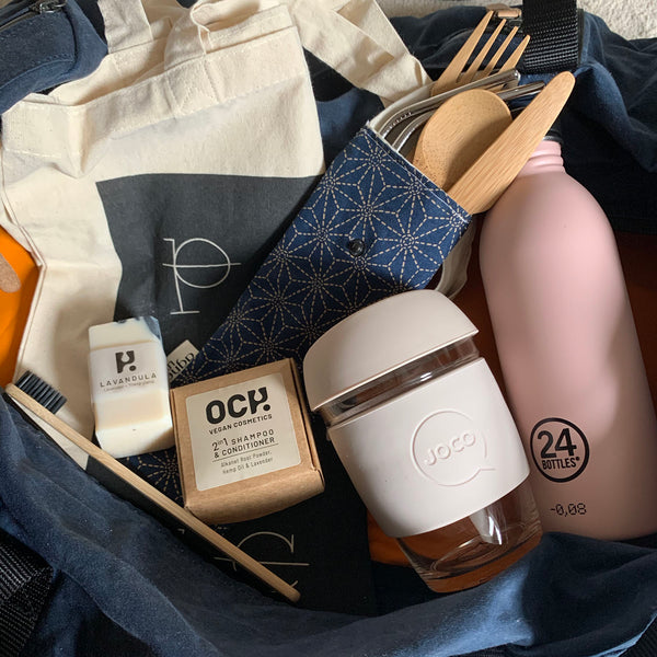 Plastic free travel essential in a duffle bag - bamboo toothbrush, soap and shampoo bars, reusable coffee cup, pink urban reusable water bottle, bamboo cutlery and stainless steel straws in navy cutlery pouch and Last branded tote bag