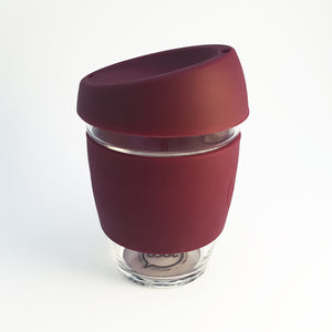 Glass reusable coffee cup with wine red silicone lid and belly band with Joco branding