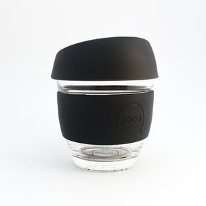 Small glass reusable coffee cup with black silicone lid and belly band with Joco branding