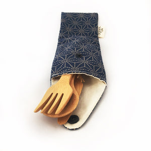 Cutlery pouche in navy blue geometric star pattern holding bamboo knife, fork and spoon.
