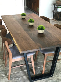Handmade dining table made from walnut and steel metal base finished in black chairs