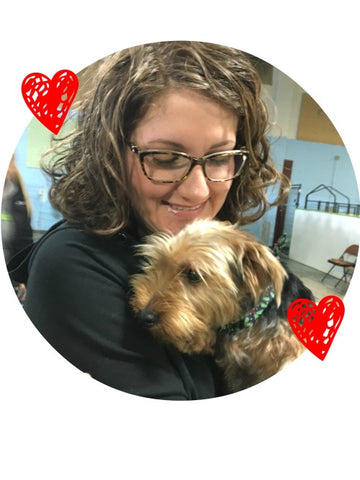 Woman with brown curly hair and glasses holding a yorkie puppy