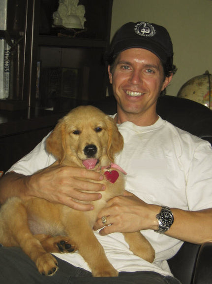 Greg Montoya Holding A Golden Retriever