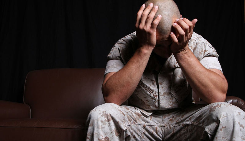 soldier with hands on face - ptsd